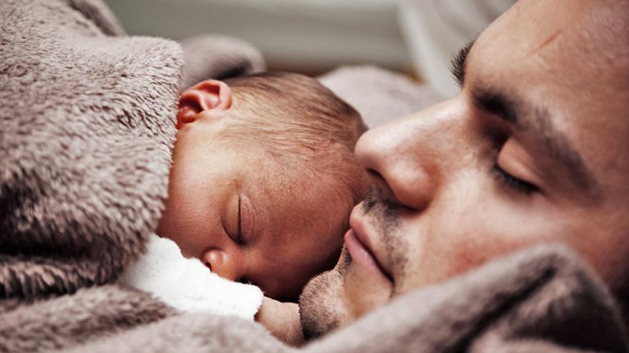 Un hombre cuida a un bebé.