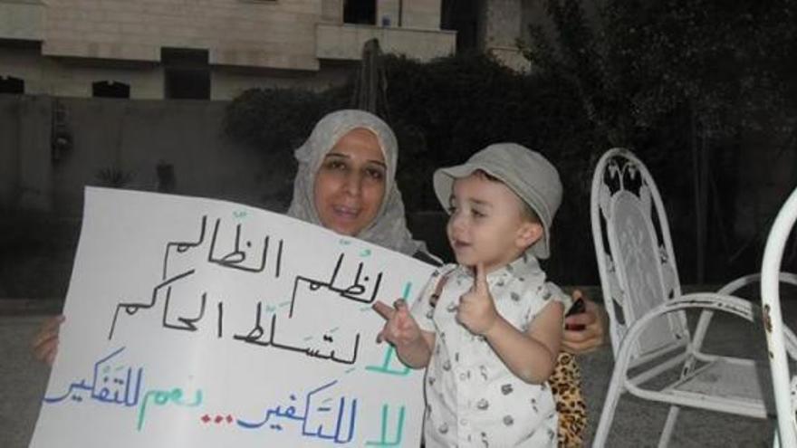 La maestra y activista de Raqqa Souad Nofal, con uno de sus carteles. Fuente: SyriaUntold