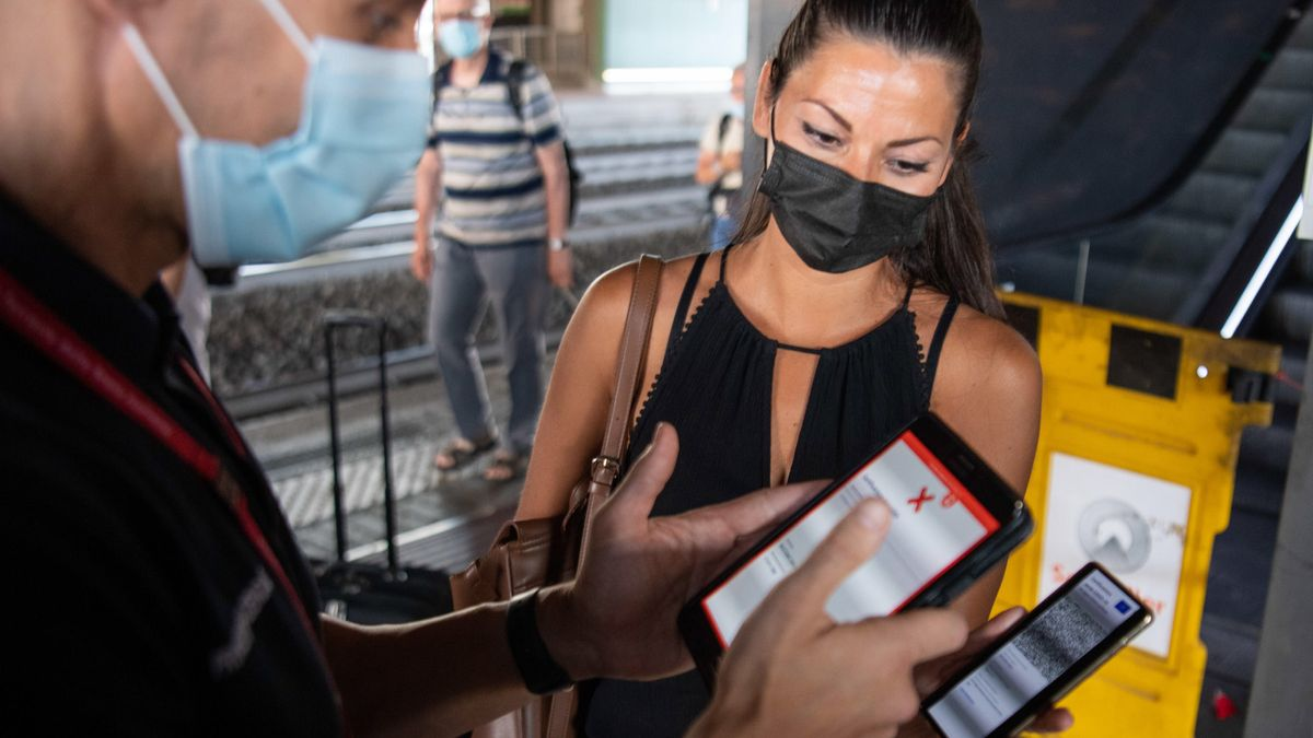 """Una pasajera muestra su """"pase verde"""" en una estación de Roma."""