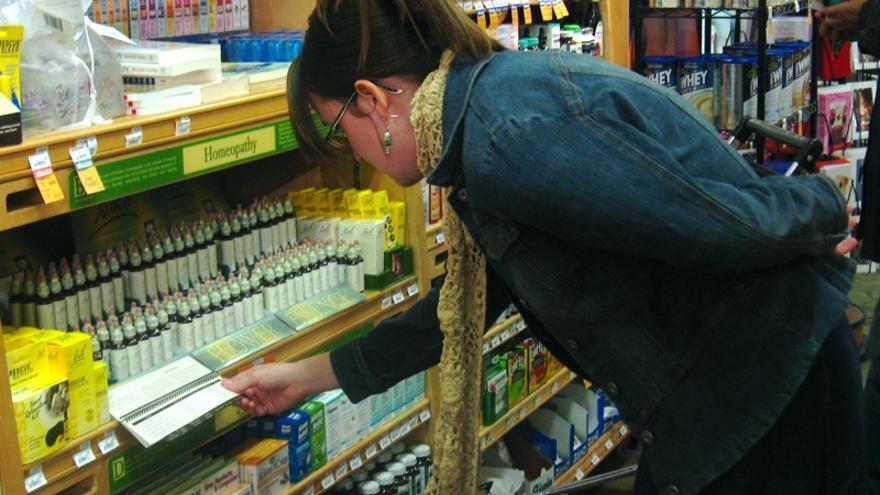 Una mujer ante un estante de homeopatía / FOTO: Casey West