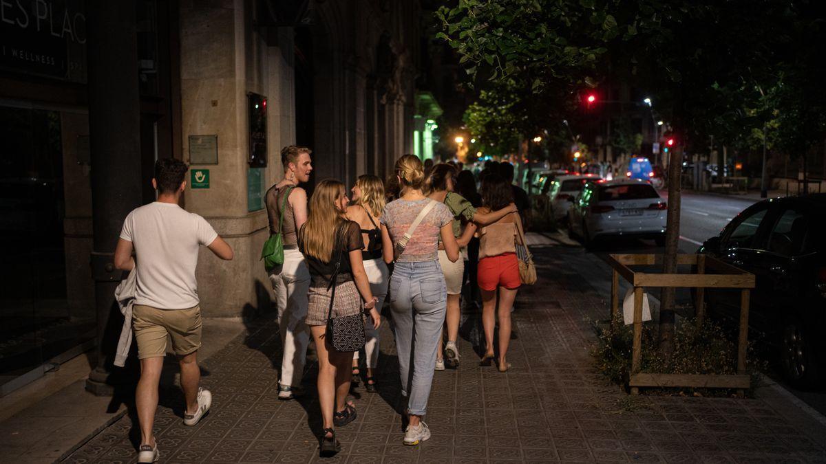 Un grupo de jóvenes pasea por la calle antes de entrar a una discoteca.