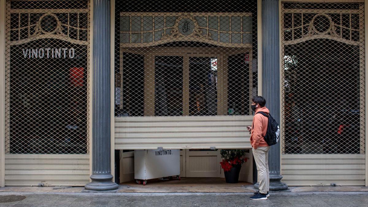 Un trabajador de un restaurante del centro de València cierra el local el día que se aplica en la Comunitat Valenciana las nuevas medidas contra la pandemia de coronavirus. EFE/Biel Aliño/Archivo