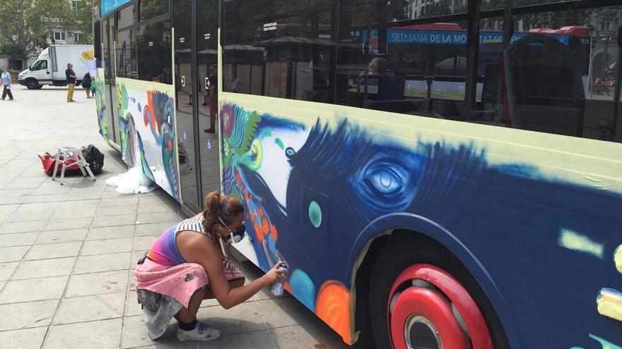 Una grafitera decora un autobús de la EMT este jueves en una de las actividades por el Día sin Coche