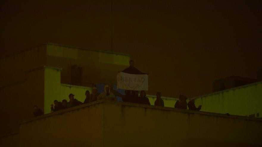 """Una de las personas que ha participado en el motín del CIE de Madrid sujeta una pancarta con el mensaje de  """"Libertad"""" / Dani Gago (Podemos)"""