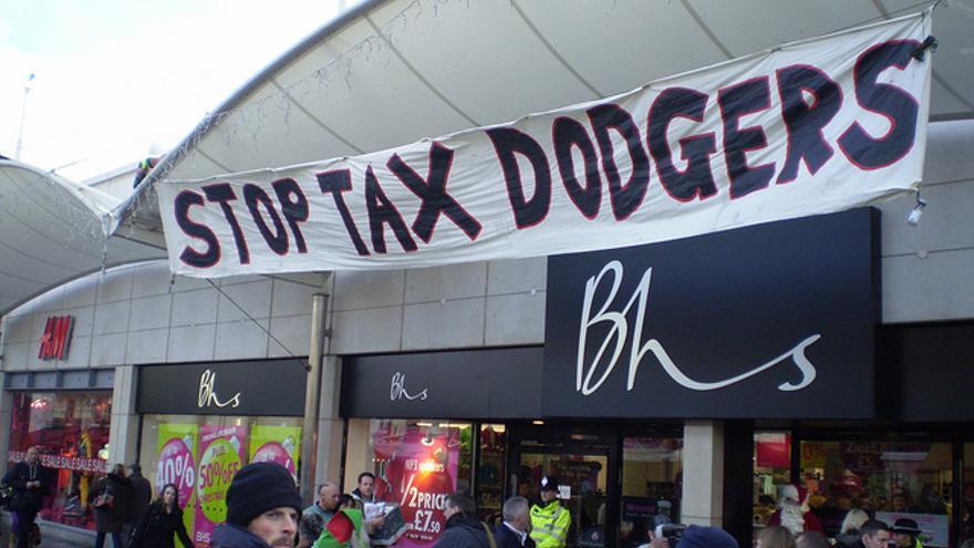 """""""Parad a los evasores fiscales"""", dice una pancarta de UK Uncut ante una cadena de tiendas."""
